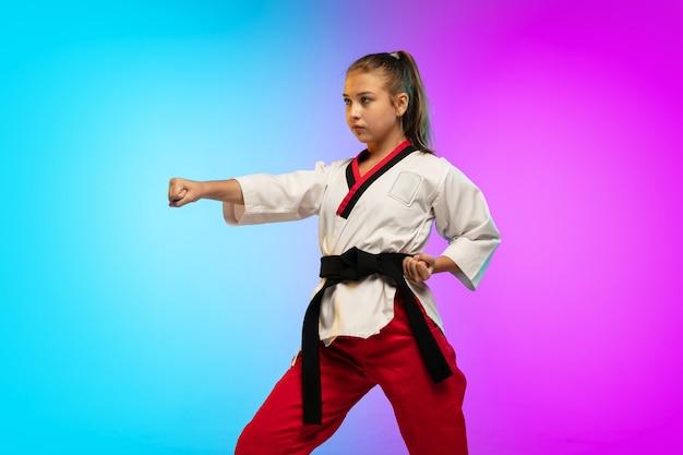 Pratica. karate, ragazza di taekwondo con cintura nera isolata su sfondo sfumato in luce al neon. piccola modella caucasica, allenamento sportivo per bambini in movimento e azione. sport, movimento, concetto di infanzia.