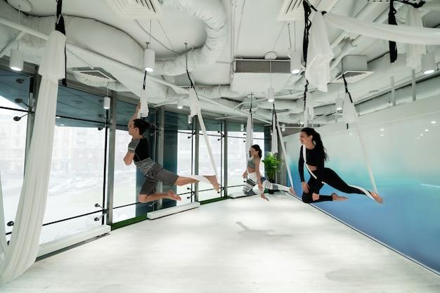 Praticare lo yoga volante. uomo dai capelli scuri e due donne che praticano yoga volante in un ampio centro fitness