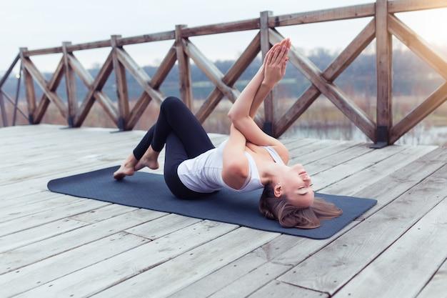Praticare yoga al mattino su un ponte di legno con alberi e raggio di sole sullo sfondo