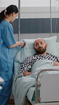 L'assistente del professionista organizza il letto del paziente per l'uomo malato durante il recupero dalla malattia monitorando i sintomi della malattia che lavora nel reparto ospedaliero. paziente ricoverato con disturbi respiratori