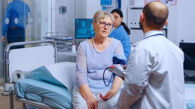 Il professionista misura la pressione sanguigna di una donna anziana in pensione con un monitor mentre l'infermiera lavora in background. sistema medico-sanitario, trattamento e diagnosi dell'esame della malattia