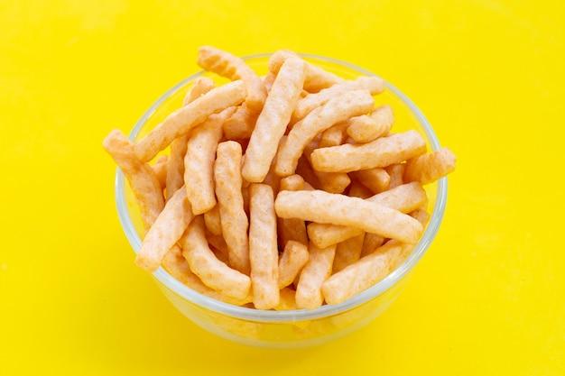 Bastoncini di cracker di gamberi in una ciotola di vetro su sfondo giallo. spuntino di riso croccante di gamberetti