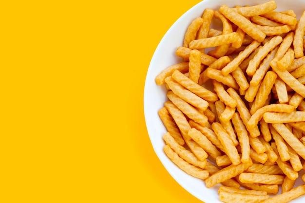 Bastoncini di cracker di gamberi su sfondo giallo. spuntino di riso croccante di gamberetti
