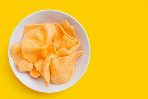 Cracker di gamberi in ciotola bianca su sfondo giallo. spuntino di riso croccante di gamberetti
