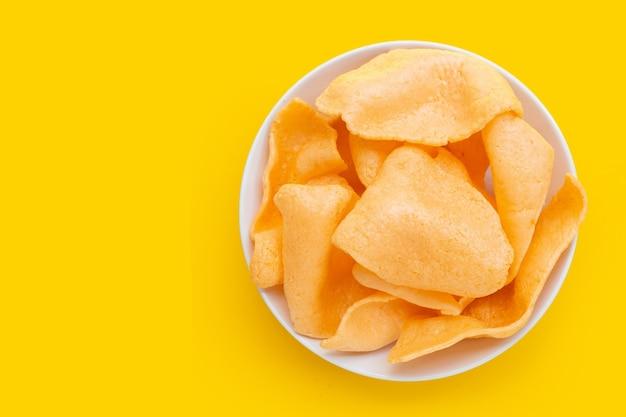 Cracker di gamberi in piastra bianca su sfondo giallo. spuntino di riso croccante di gamberetti