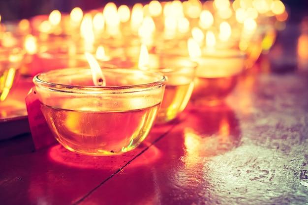Preghi il vetro della candela sulla tavola di legno in tempio cinese
