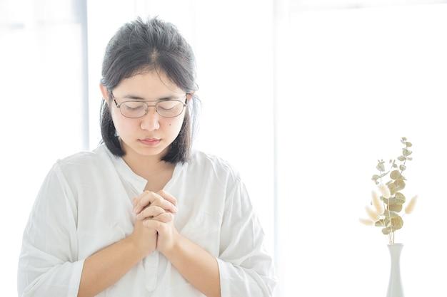 La ragazza della preghiera adora dio e prega da casa per il coronavirus covid-19. pregare a casa, chiesa online, mani in preghiera, adorazione a casa