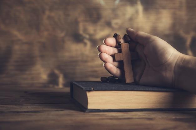 Donna di preghiera che tiene croce sulla bibbia