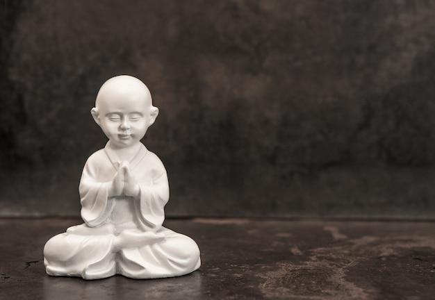 Pregare buddha. statua del monaco bianco su sfondo scuro. concetto di meditazione