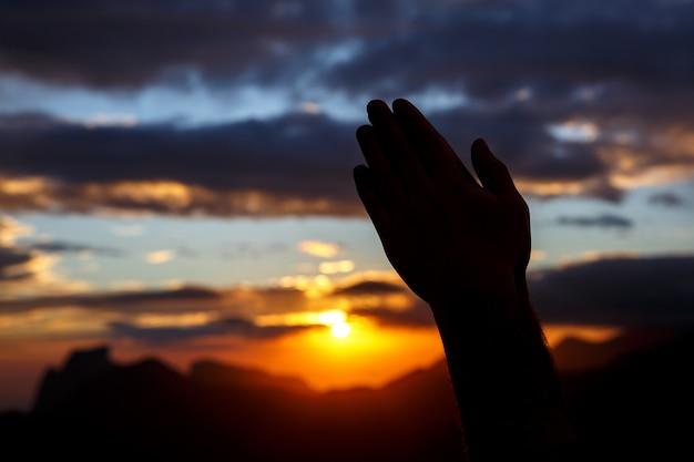 Pregare le mani sullo sfondo del tramonto. sagoma nera