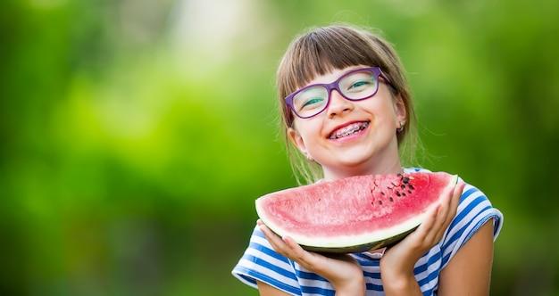 Ragazza preadolescente in giardino con in mano una fetta di anguria bambina felice che mangia anguria ragazza bambina...