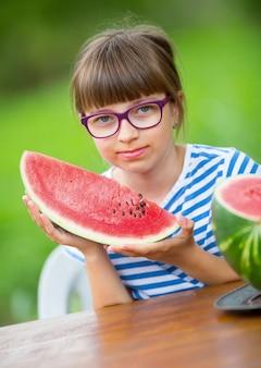 Ragazza pre-adolescente in giardino con in mano una fetta di anguria bambina felice che mangia anguria