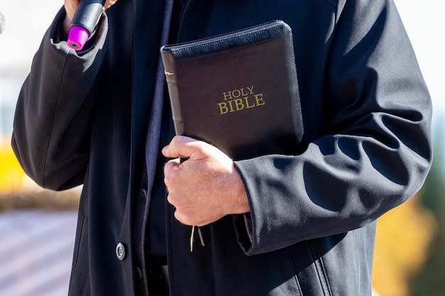 Predicatore con bibbia e microfono durante il sermone