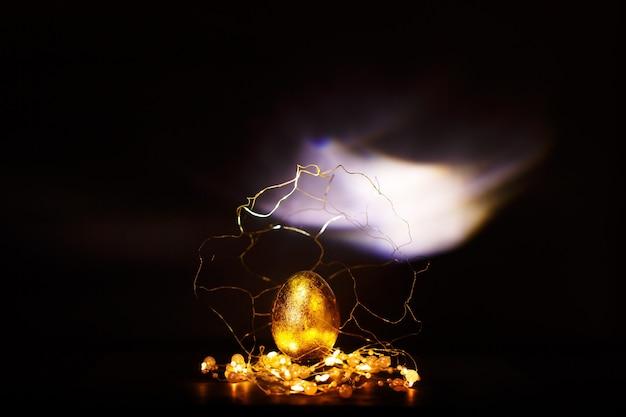 Prezioso uovo di pasqua dorato con decorazioni in oro su sfondo scuro