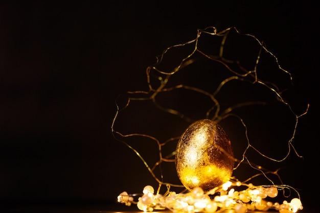 Prezioso uovo di pasqua dorato con decorazioni in oro con luci su sfondo scuro