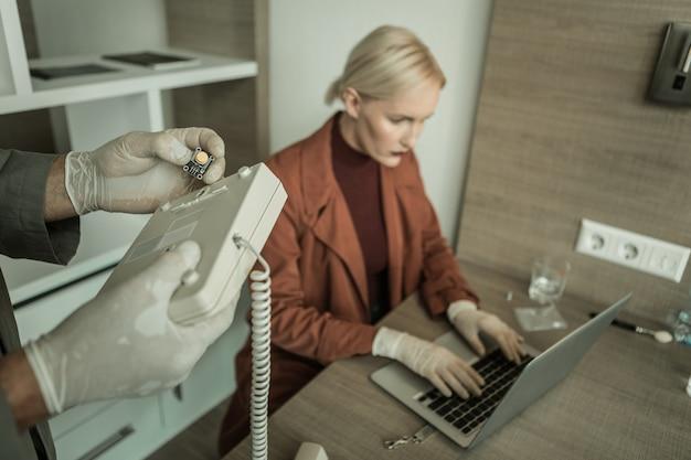 Ispezionare accuratamente l'attrezzatura. spia esecutiva che installa il chip all'interno del telefono mentre il suo compagno di lavoro lavora con l'hacking del computer