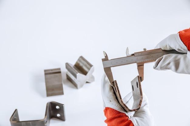 Misurazione precisa di parti metalliche su sfondo bianco utilizzando un calibro a corsoio