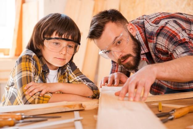 La precisione è la parte più importante della carpenteria. giovane carpentiere maschio concentrato che mostra a suo figlio come lavorare con il legno in officina