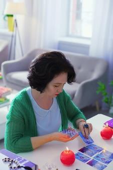 Previsione del futuro. intelligente e talentuosa cartomante che mette le carte dei tarocchi sul tavolo mentre fa il suo lavoro
