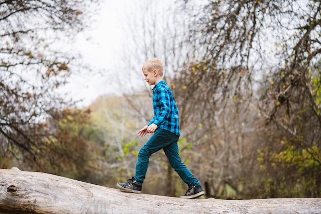 Preeteen attività bambino maschio in natura. un ragazzo che cammina su un tronco d'albero caduto sullo sfondo della foresta autunnale