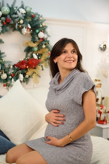 Concetto di gravidanza, di feste, della gente e di aspettativa - donna incinta felice che si siede e che tocca la sua pancia a casa sopra il fondo di natale.