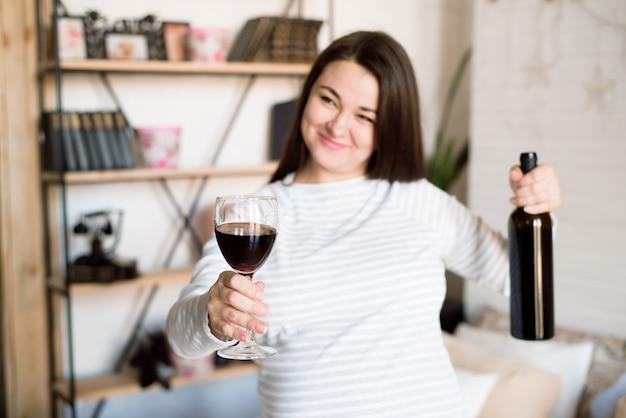 La donna incinta alcolica sta versando il vino da una bottiglia in un bicchiere e sta bevendo