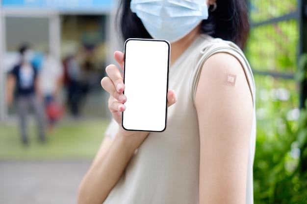 Una madre asiatica incinta in un abito lungo mostra lo schermo del suo smartphone e il gesso dopo aver ricevuto la vaccinazione.