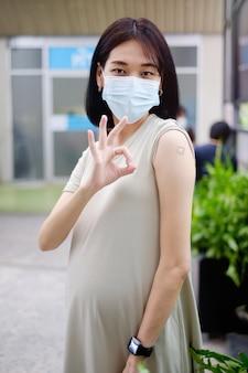 Una madre asiatica incinta in un lungo abito è in piedi per mostrare il suo gesto ok e mostrando il gesso dopo aver ricevuto la vaccinazione.