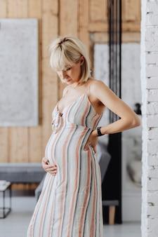 Donna incinta dai capelli biondi in un soggiorno