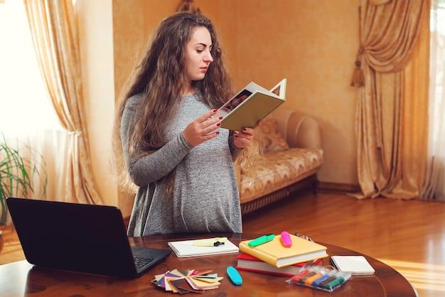 Donna incinta di affari che utilizza un computer portatile e lavora a casa. donna che fa shopping online. gravidanza, lavoro e concetto di acquisto. donna incinta che studia online a casa.