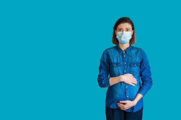 La donna caucasica incinta che indossa una mascherina medica è in posa da parte su sfondo blu