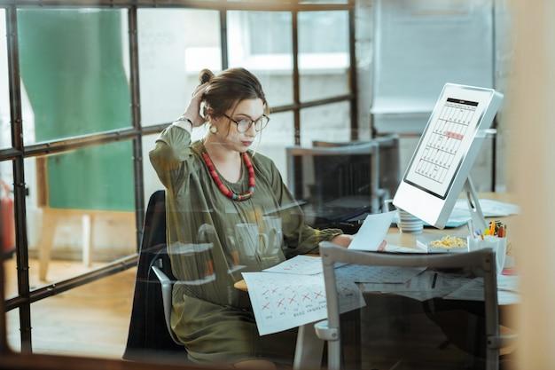 Stilista incinta. interior designer incinta che indossa una bella collana rossa che lavora sodo sul suo programma on
