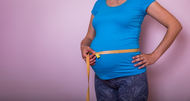 Pancia di pancia di misurazione femminile incinta con il centimetro giallo. terzo trimestre e metro, nuovo concetto di maternità vitale.