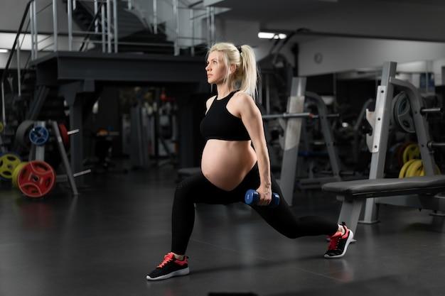 Donna incinta fitness facendo esercizi di affondi per allenamento allenamento muscolare gamba in palestra