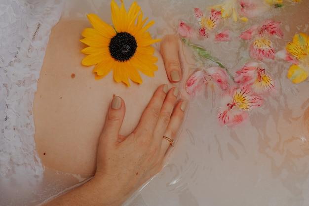 Ragazza incinta in un bagno con latte e fiori