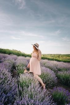 Bionda incinta della ragazza in un vestito beige e cappello di paglia. campo di lavanda in previsione di un bambino. l'idea di un servizio fotografico. passeggiata al tramonto. futura mamma cesto di fiori.