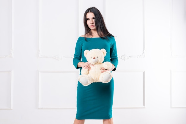 Una ragazza incinta in un vestito con un orsacchiotto in mano. foto di alta qualità
