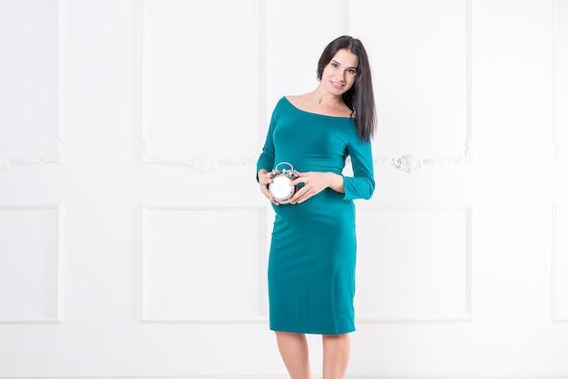 Una ragazza incinta in un vestito, con un orologio tra le mani. foto di alta qualità