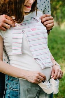 La ragazza incinta e il marito delle mani tengono l'abbraccio, per mettere scarpe da bambino e vestiti sullo stomaco, aspettando il bambino.