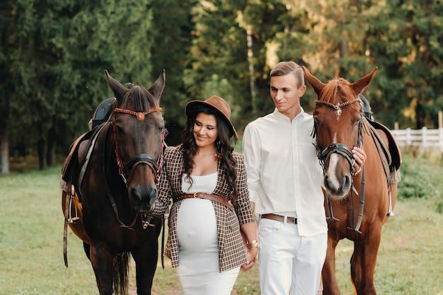 Una ragazza incinta con un cappello e suo marito in abiti bianchi stanno accanto ai cavalli nella foresta in natura.