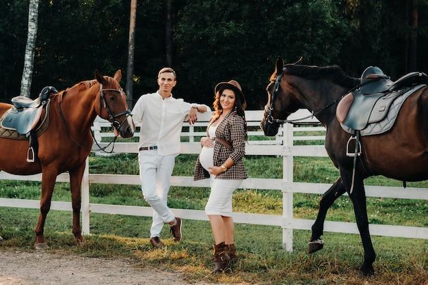 Una ragazza incinta in un cappello e un uomo in vestiti bianchi stanno accanto ai cavalli vicino a un recinto bianco. elegante donna incinta con un uomo con i cavalli. coppia sposata.