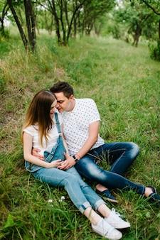 La ragazza incinta e suo marito sono felici di abbracciarsi, tenere le mani sullo stomaco, seduti sull'erba all'aperto sulla superficie del giardino