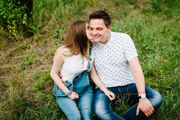 La ragazza incinta e suo marito sono felici di abbracciarsi, tenersi per mano, sulla pancia, seduti sull'erba all'aperto in giardino