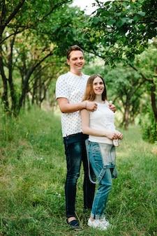 La ragazza incinta e il marito si tengono per mano abbracciati, per mettere scarpe e vestiti per bambini sullo stomaco, in attesa del bambino