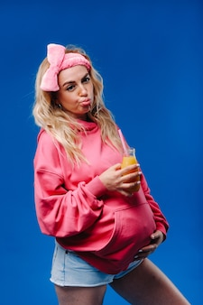 Ragazza incinta in abiti rosa con una bottiglia di succo su sfondo blu.
