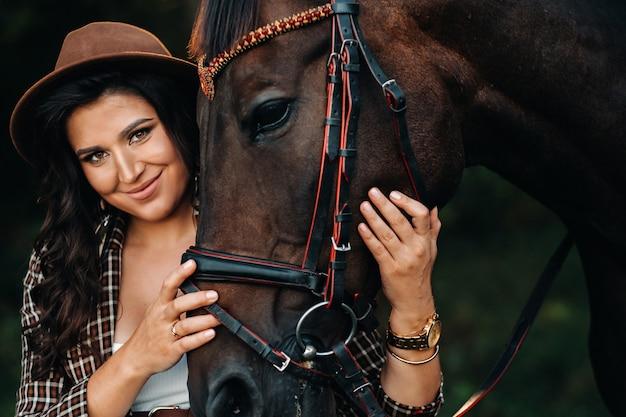 Ragazza incinta con una grande pancia in un cappello accanto ai cavalli nella foresta in natura. elegante ragazza in abiti bianchi e una giacca marrone.