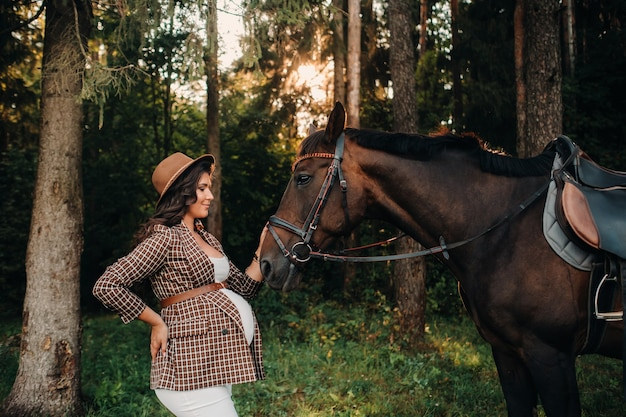 Ragazza incinta con una grande pancia in un cappello accanto ai cavalli nella foresta in natura. una donna incinta alla moda in un vestito bianco e giacca marrone con i cavalli.