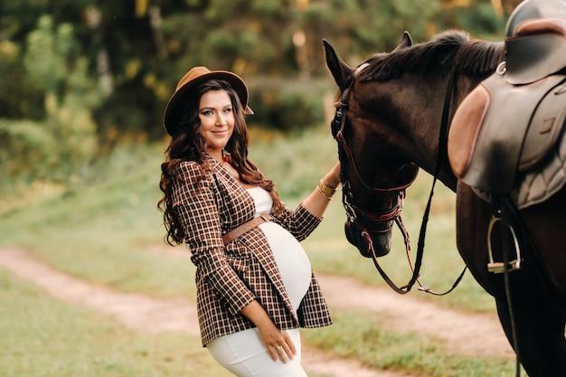 Ragazza incinta con una grande pancia in un cappello accanto ai cavalli nella foresta in natura.