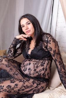 Ragazza incinta con una grande pancia in vestaglia. riposo sul letto. foto di alta qualità