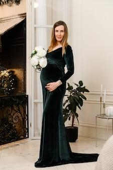 Ragazza incinta con fiori e in un abito di velluto